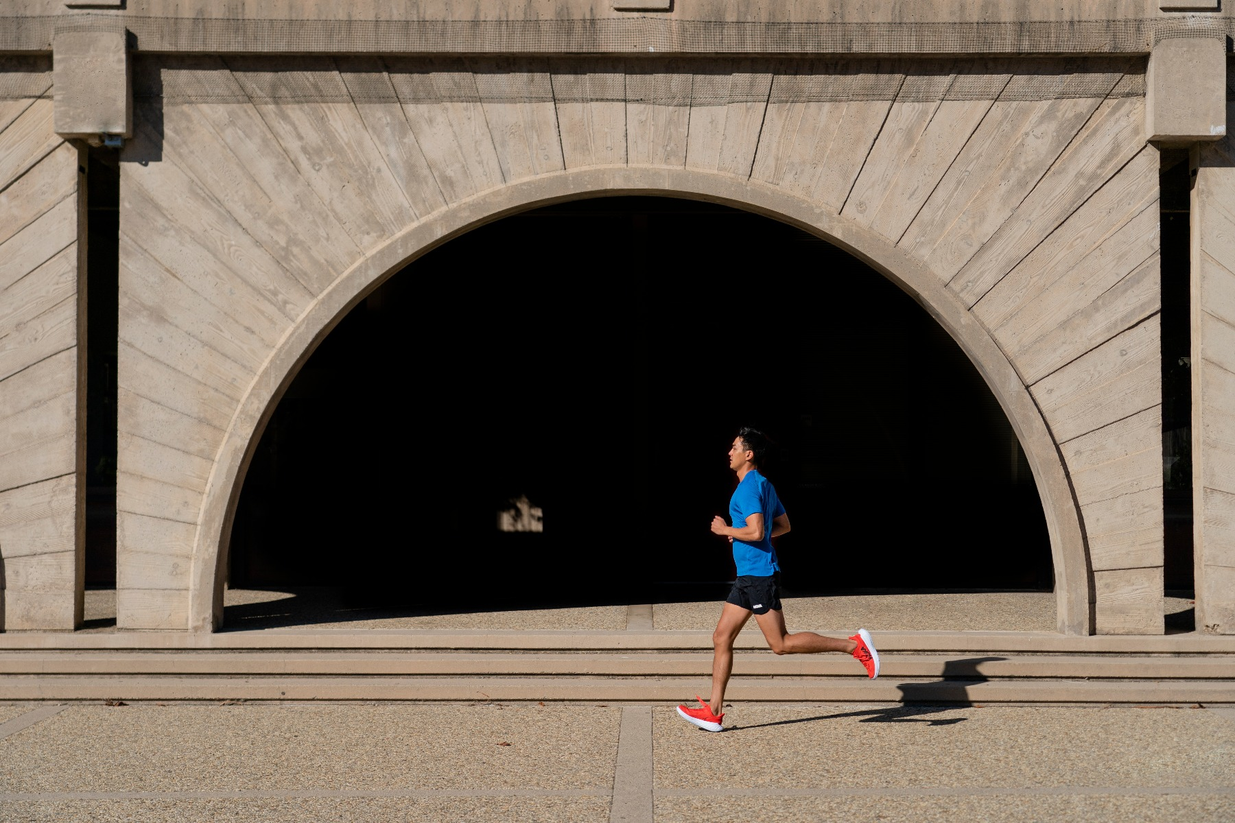 Man running in front of tunnel wearing HOKA's Carbon X 2